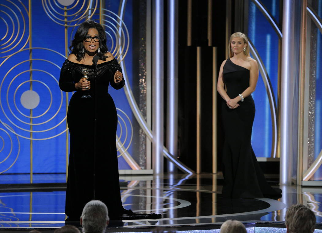 This image released by NBC shows Oprah Winfrey accepting the Cecil B. DeMille Award as presenter Reese Witherspoon looks on, right, at the 75th Annual Golden Globe Awards in Beverly Hills, Calif., ...