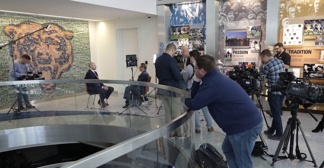 New Chicago Bears head coach Matt Nagy, second from left, is interviewed by a local television station while others wait after an NFL football news conference Tuesday, Jan. 9, 2018, in Lake Forest ...