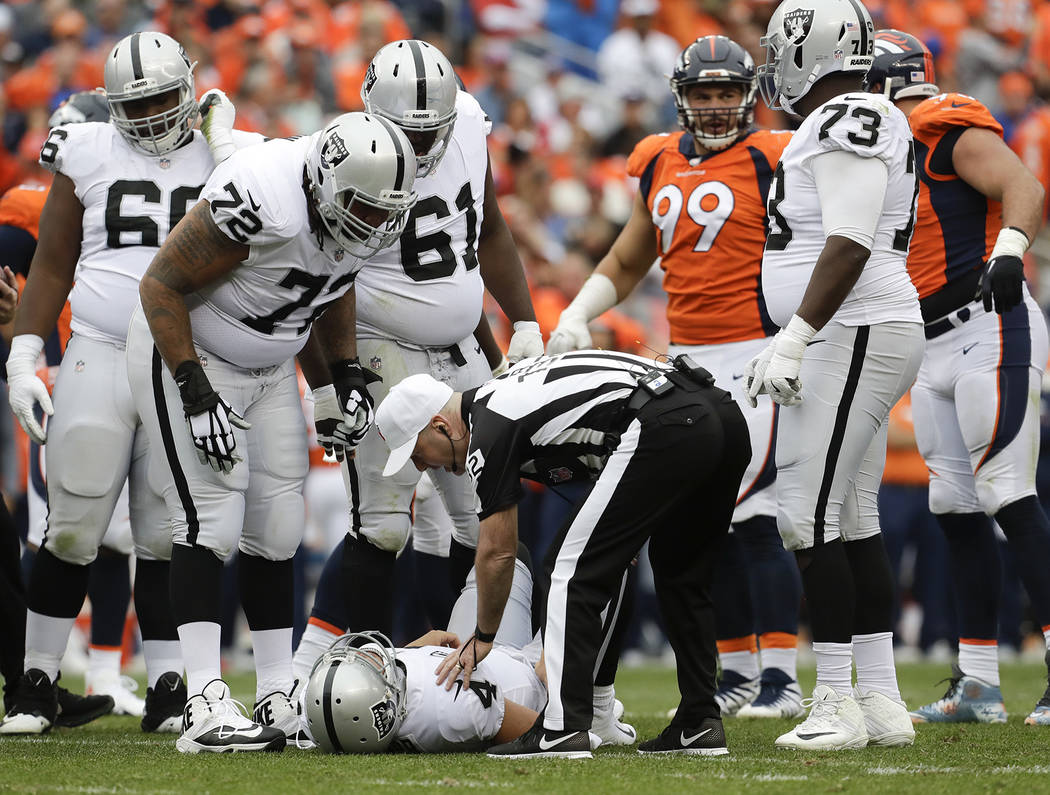 Oakland Raiders quarterback Derek Carr lays the field after being injured during the second half of an NFL football game against the Denver Broncos Sunday Oct. 1 2017 in Denver. (AP