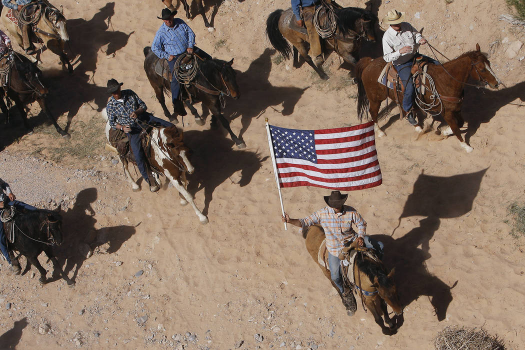 FILE - In this April 12, 2014, file photo, the Bundy family and their supporters fly the American flag as their cattle is released by the Bureau of Land Management back onto public land outside of ...