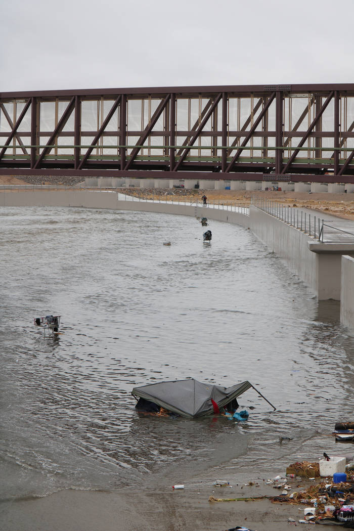 A tent and several shopping carts are caught in floodwaters above a detention basin near east Cheyenne Avenue along the Las Vegas Wash on Tuesday, Jan. 9, 2018. About a mile downstream, rescue cre ...