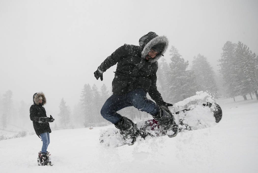 Gerardo Guerrero of Venezuela snowboards as Osmery Garcia looks on at Upper Lee Meadows in Lee Canyon outside of Las Vegas, Tuesday, Jan. 9, 2018. Richard Brian Las Vegas Review-Journal @vegasphot ...