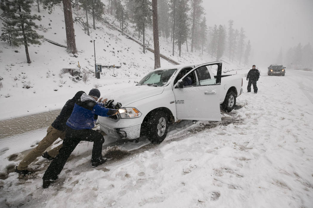 Volunteers help a motorist after his vehicle was stuck in the snow at Upper Lee Meadows in Lee Canyon outside of Las Vegas, Tuesday, Jan. 9, 2018. Richard Brian Las Vegas Review-Journal @vegasphot ...