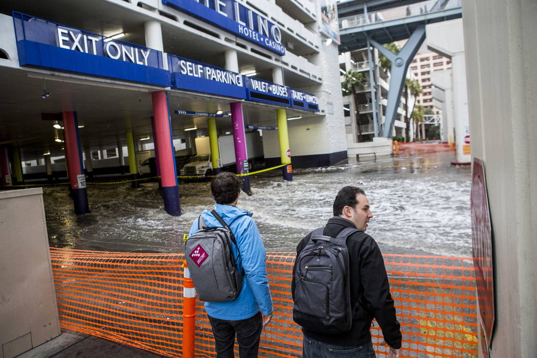 Jon, left, and Ben Gaiser, who are both attending CES, watch flood waters rush by The Linq Hotel in Las Vegas on Tuesday, Jan. 9, 2018. Patrick Connolly Las Vegas Review-Journal @PConnPie