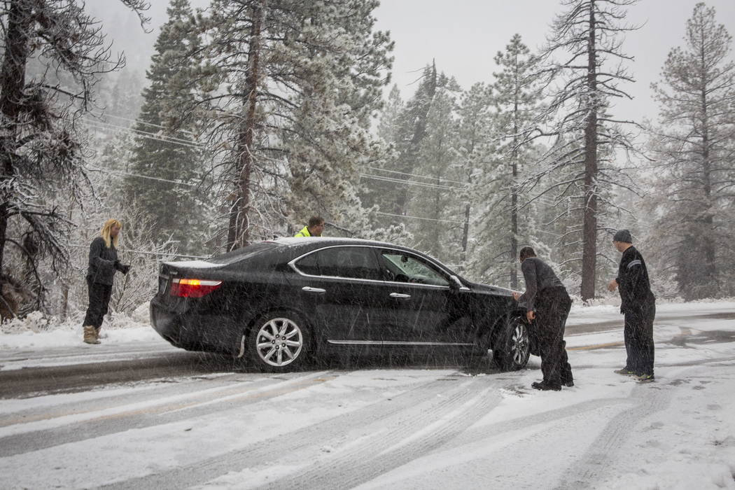 People attempt to push a Lexus out of the snow at Mount Charleston on Tuesday, Jan. 9, 2018. Patrick Connolly Las Vegas Review-Journal @PConnPie