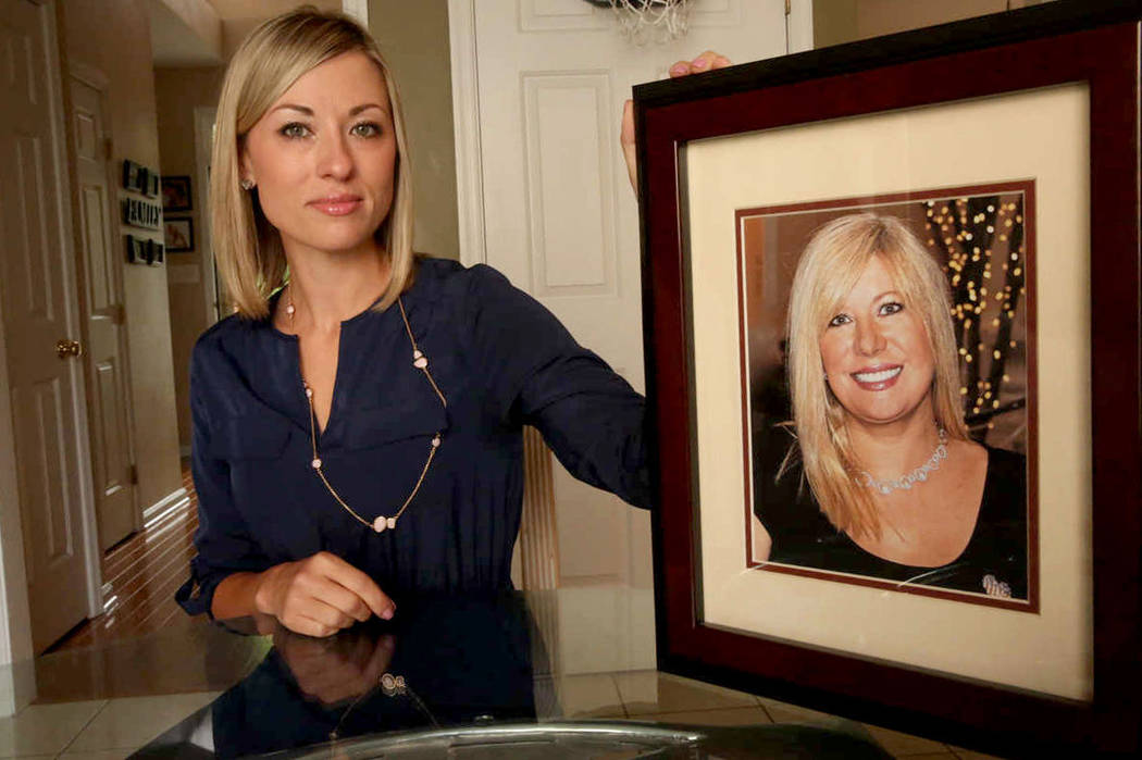 In this May 25, 2016, photo, Kim Pack poses with a photo of her late mother, talk-show host April Kauffman, in Linwood, N.J. Pack's stepfather, Dr. James Kauffman, was charged in the murder of her ...