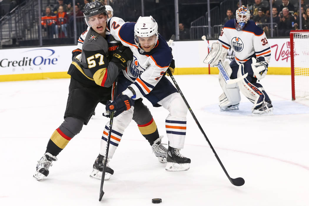 Vegas Golden Knights left wing David Perron (57) and Edmonton Oilers defenseman Kris Russell (4) vie for the puck as Oilers goaltender Cam Talbot (33) defends the net during the first period of an ...