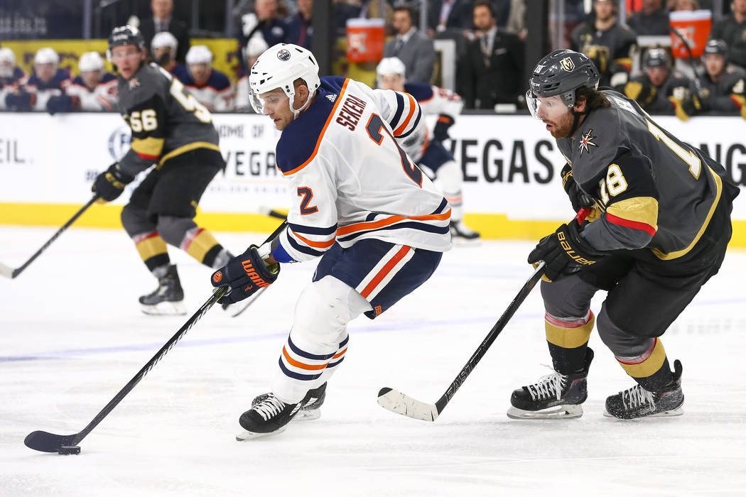 Edmonton Oilers defenseman Andrej Sekera (2) controls the puck as Vegas Golden Knights left wing James Neal (18) closes in during the second period of an NHL hockey game between the Vegas Golden K ...