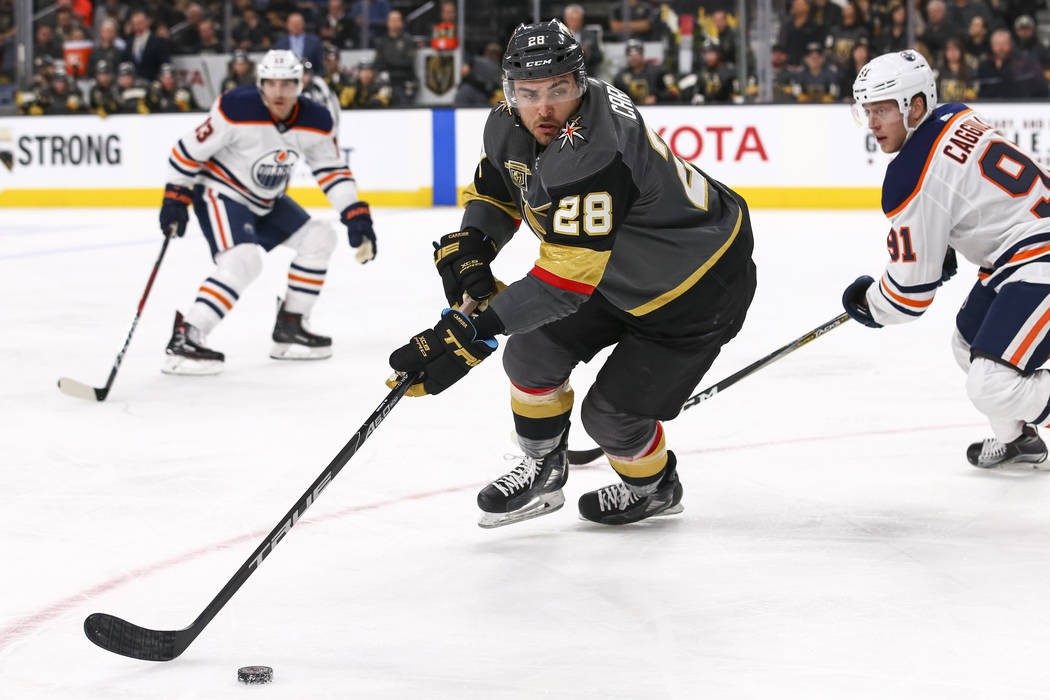Vegas Golden Knights left wing William Carrier (28) controls the puck as Edmonton Oilers left wing Drake Caggiula (91) trails behind during the second period of an NHL hockey game between the Vega ...