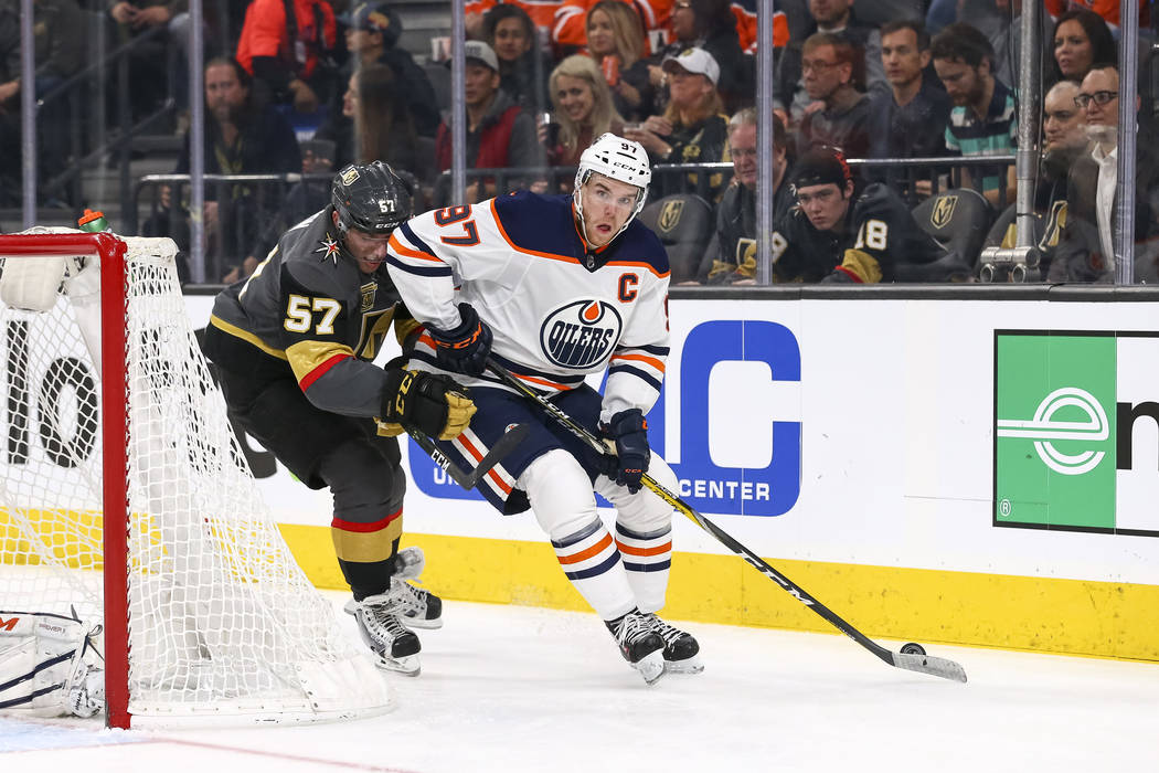 Edmonton Oilers center Connor McDavid (97) keeps the puck away from Vegas Golden Knights left wing David Perron (57) during the second period of an NHL hockey game between the Vegas Golden Knights ...