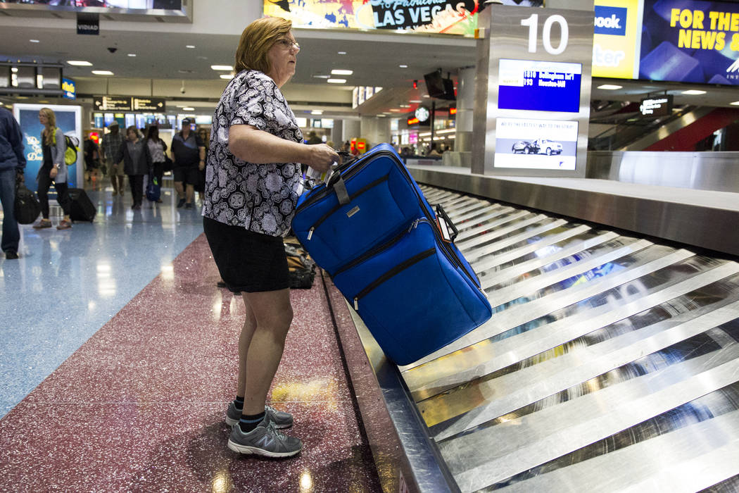 Allegiant Air passenger Michele Connelly of Richmond, Va.,  picks up her luggage at McCarran International Airport in Las Vegas on Wednesday, Aug. 9, 2017. (Erik Verduzco/Las Vegas Review-Journal) ...