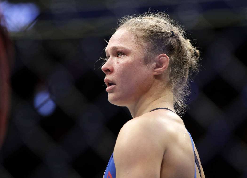 FILE - In this Dec. 30, 2016, file photo Ronda Rousey stands in the cage after Amanda Nunes forced a stoppage in the first round of their women's bantamweight championship mixed martial arts bout  ...