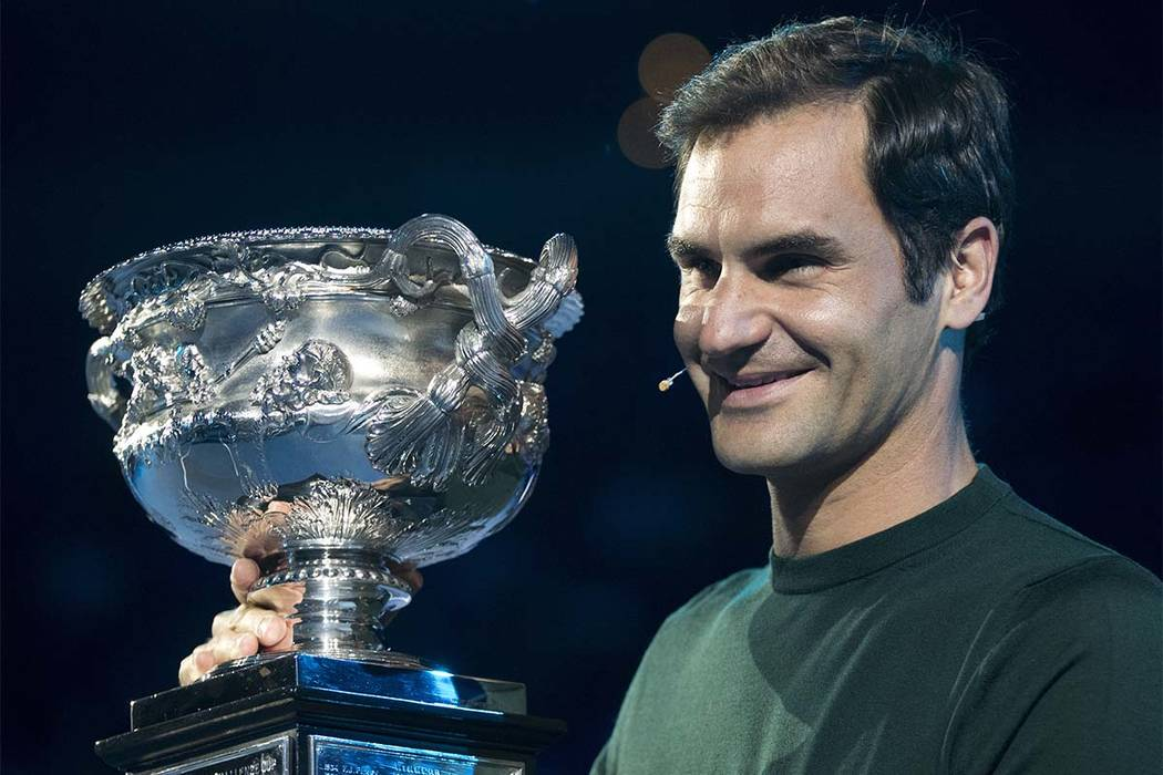 Defending men's singles champion Switzerland's Roger Federer poses for a photo with his trophy during a ceremony for the official draw at the Australian Open tennis championships in Melbourne, Aus ...