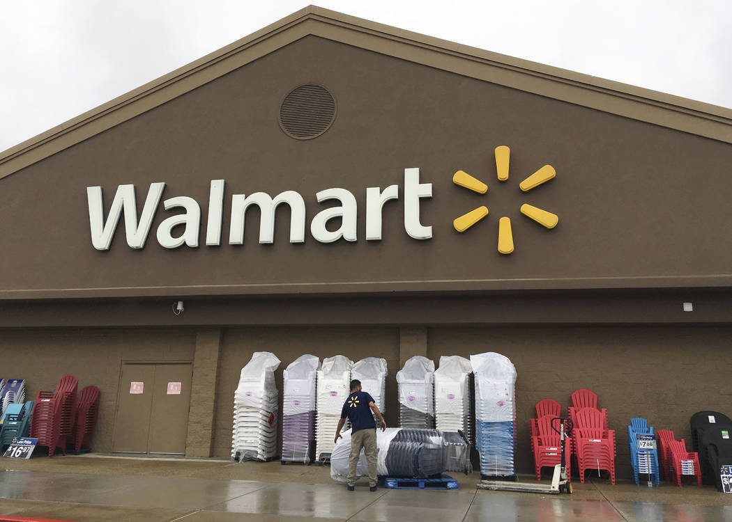 A worker stacks merchandise outside a Walmart in Salem, N.H., June 5, 2017. Walmart is boosting its starting salary for U.S. workers to $11 an hour, giving a one-time $1,000 cash bonus to eligible ...