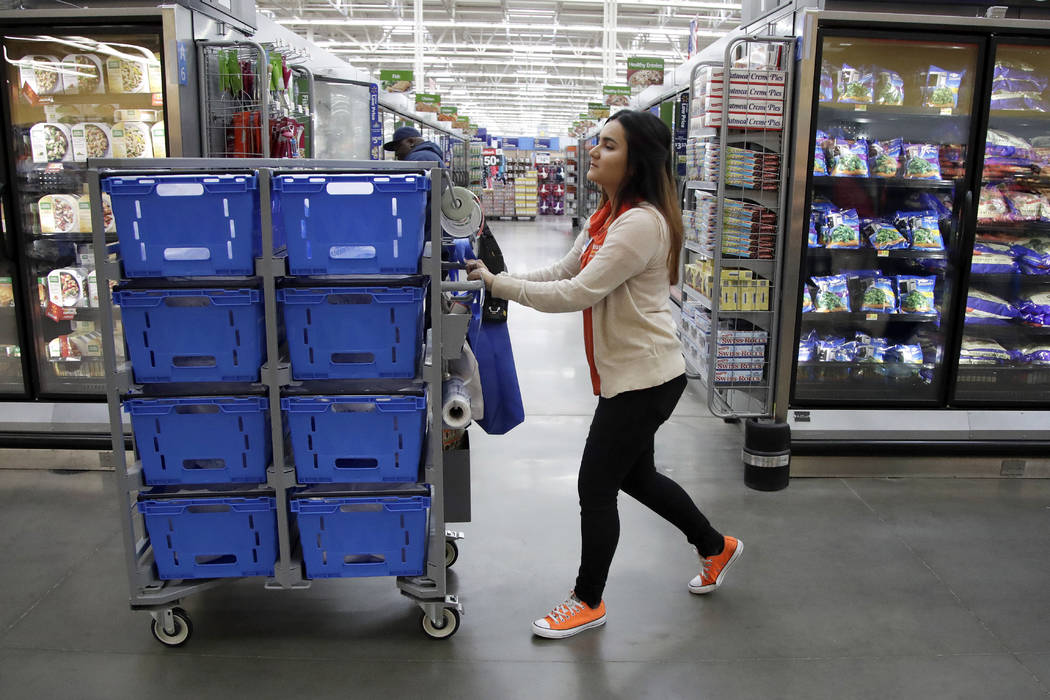 Laila Ummelaila, a personal shopper at the Walmart store in Old Bridge, N.J., pushes a cart with bins as she shops for online shoppers, Nov. 9, 2017. On Thursday, Jan. 11, 2018, Walmart announced  ...