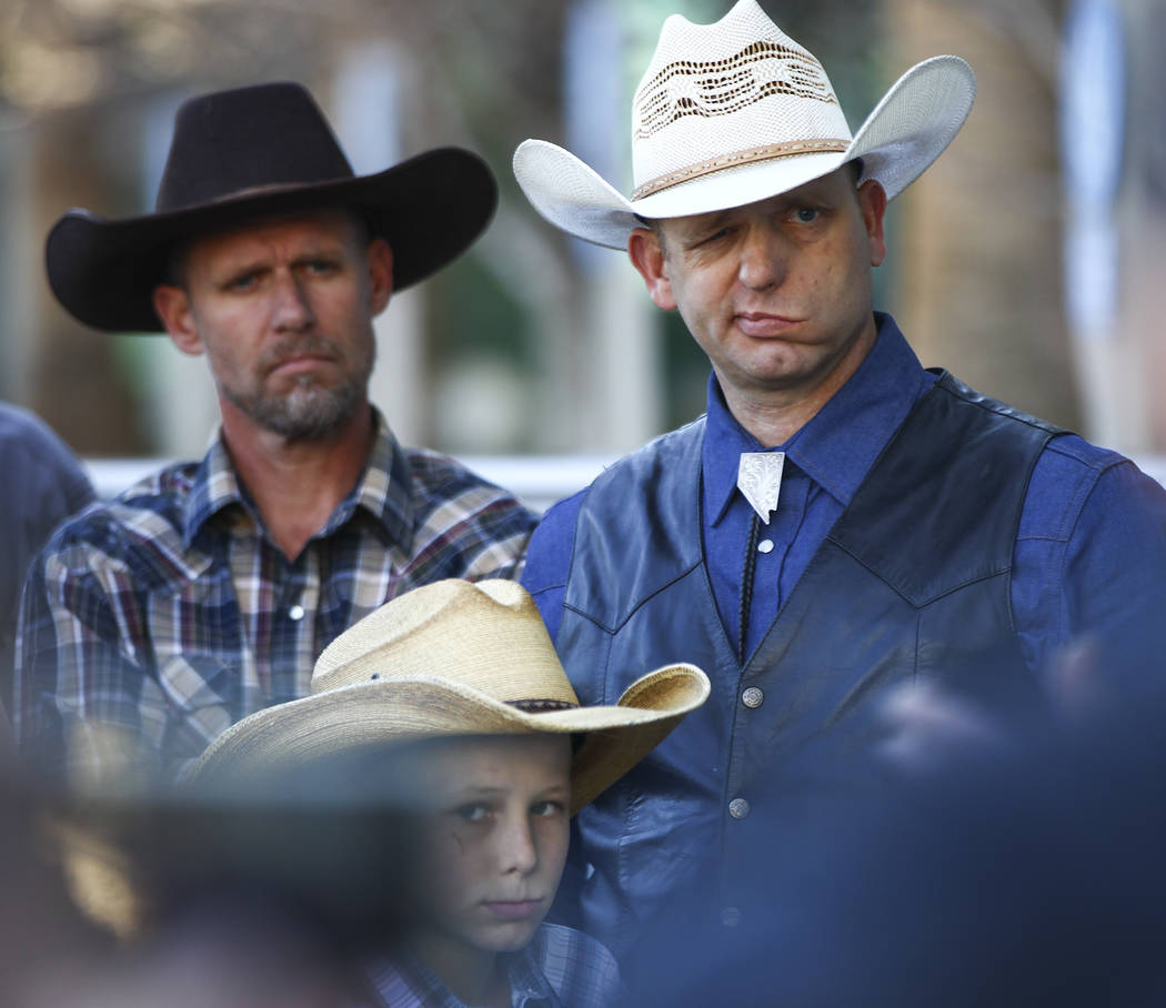 Ryan Bundy, son of rancher Cliven Bundy, right, listens to his father speak at Las Vegas Metropolitan Police Department headquarters two days after federal charges were dismissed against both of t ...