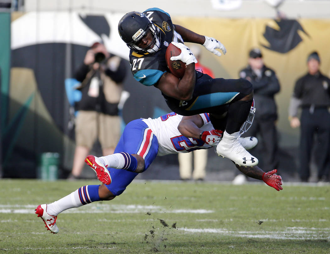 Jacksonville Jaguars running back Leonard Fournette (27) makes a reception over Buffalo Bills defensive back Leonard Johnson in the second half of an NFL wild-card playoff football game, Sunday, J ...