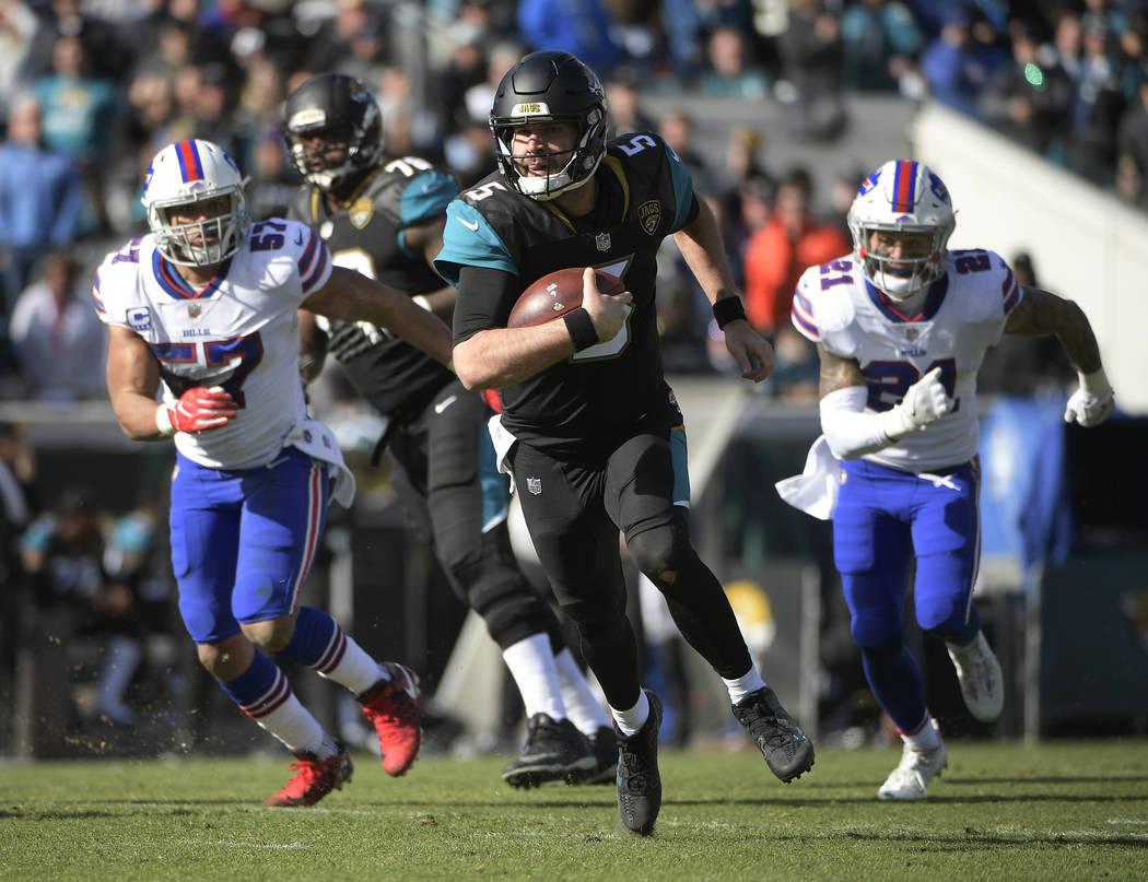 Jacksonville Jaguars quarterback Blake Bortles (5) rushes for yardage past Buffalo Bills outside linebacker Lorenzo Alexander (57) and free safety Jordan Poyer (21) in the first half of an NFL wil ...