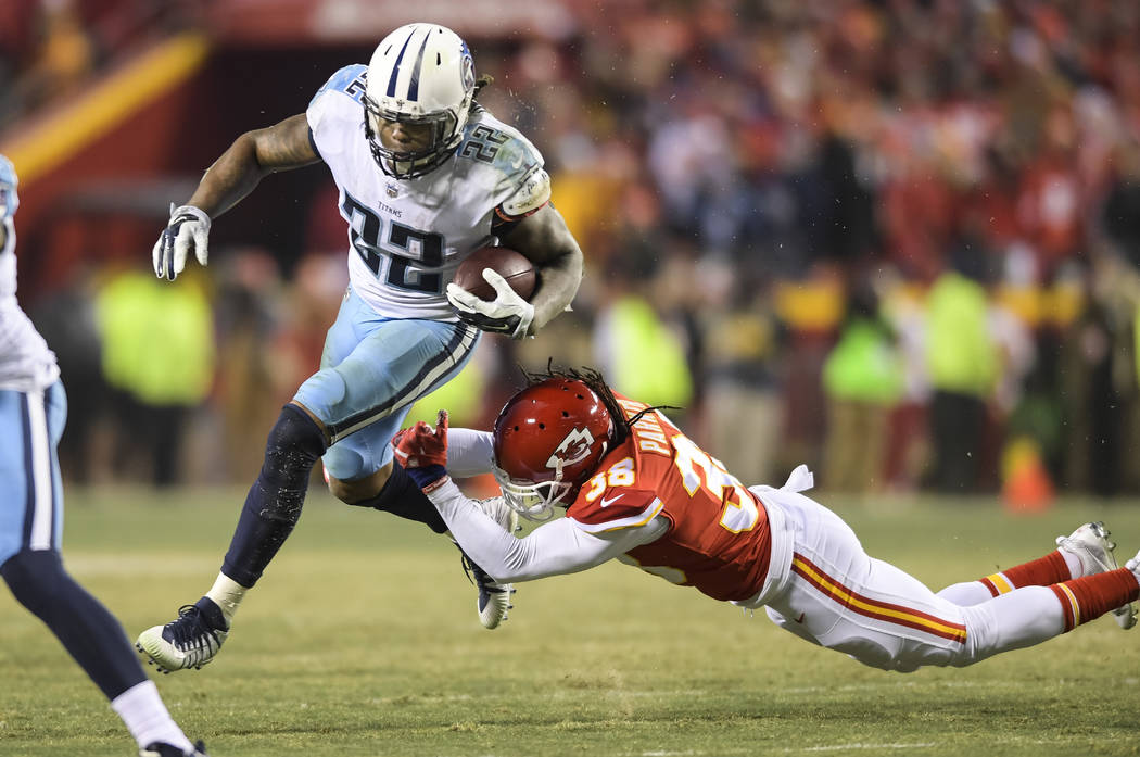 Tennessee Titans running back Derrick Henry (22) evades a tackle by Kansas City Chiefs free safety Ron Parker (38) during the second half of an NFL wild-card playoff game in Kansas City, Mo., Satu ...