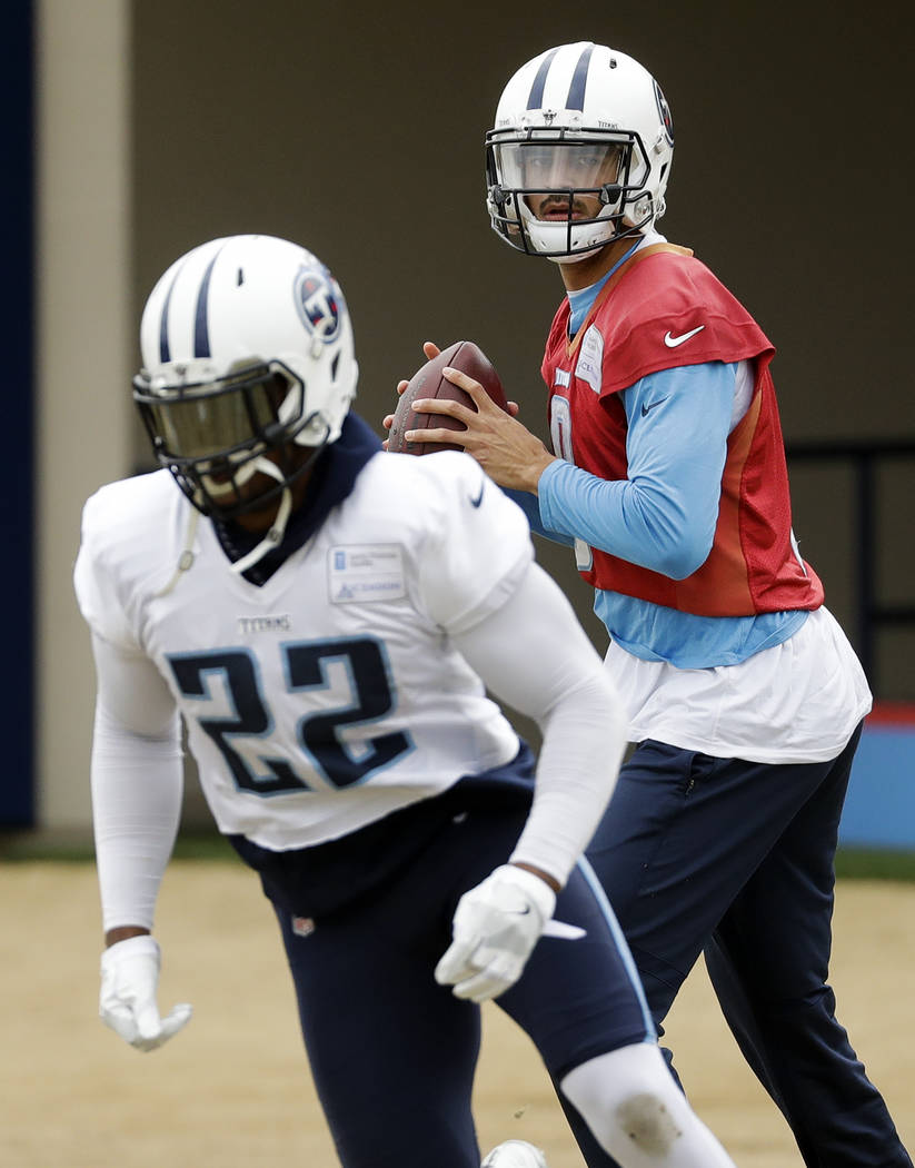 Tennessee Titans quarterback Marcus Mariota (8) runs a drill with running back Derrick Henry (22) during an NFL football practice Wednesday, Jan. 10, 2018, in Nashville, Tenn. The Titans are sched ...