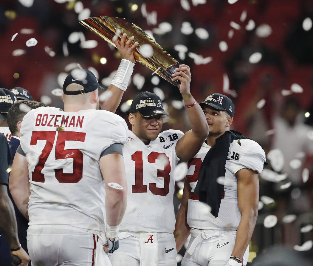 Alabama's Tua Tagovailoa holds up the championship trophy after overtime of the NCAA college football playoff championship game against Georgia Monday, Jan. 8, 2018, in Atlanta. Alabama won 26-23. ...