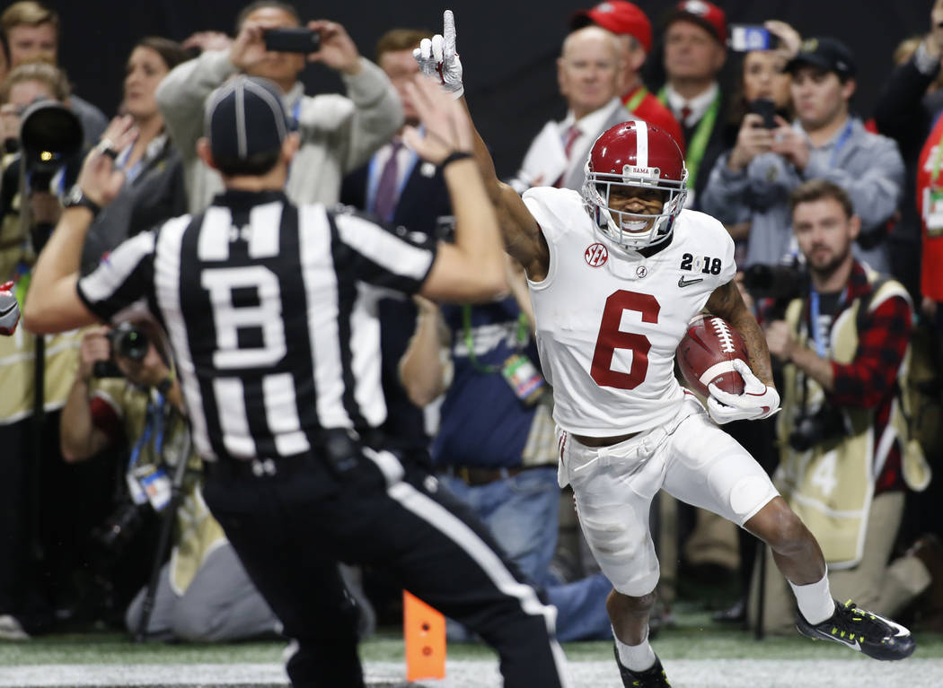 Alabama wide receiver DeVonta Smith (6) celebrates after making the game winning catch off a pass from Alabama quarterback Tua Tagovailoa (13) in overtime of the NCAA Championship game between Geo ...