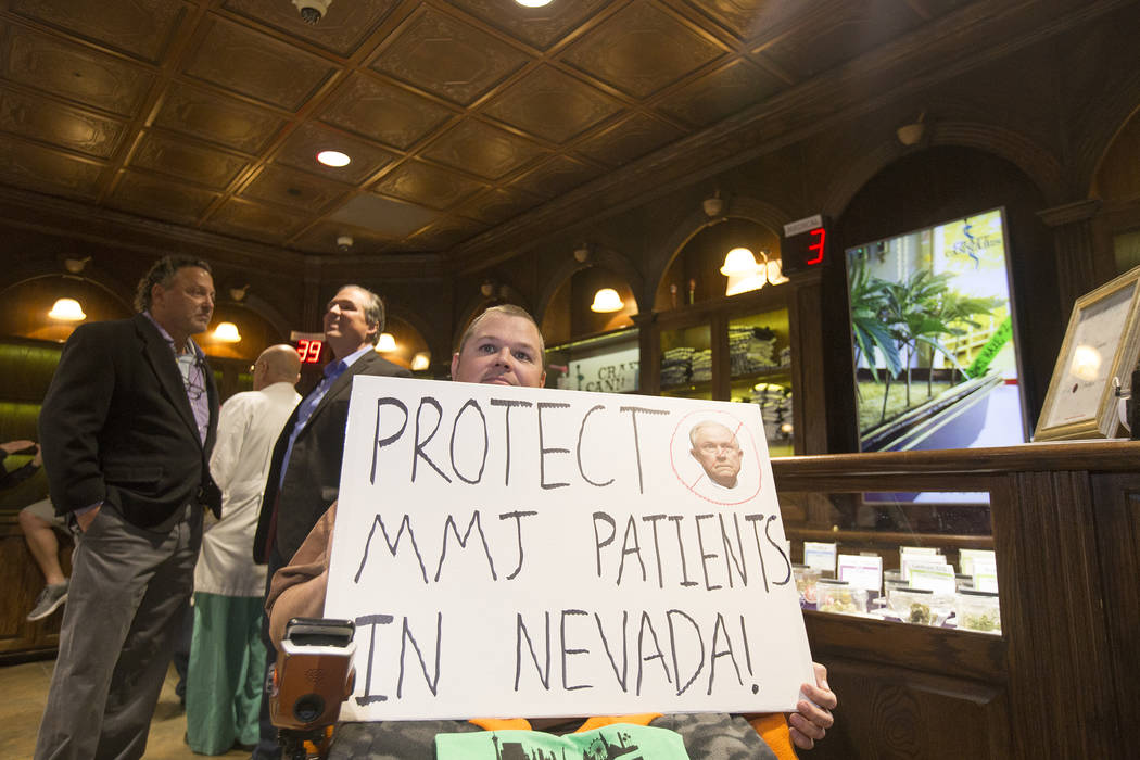 Peter Loughead, a member of the Las Vegas NORML,  a group that works to reform marijuana laws, holds a sign protesting Jeff Sessions' recent decision to lift an Obama-era policy that provided prot ...