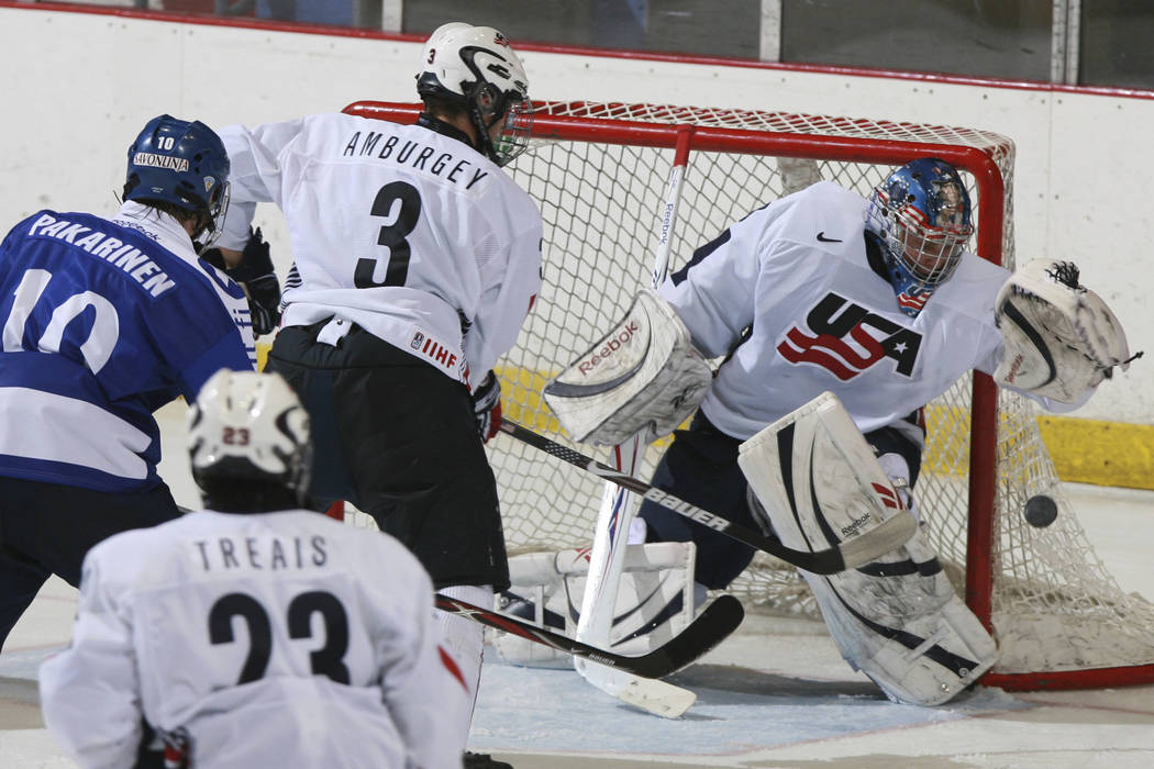 In this Nov. 8, 2008, file photo, United States' goalie Brandon Maxwell catches the puck as Tyler Amburgey (3) moves in to defend against Finland's Joonas Hurri (3) while United States' A.J. Treai ...