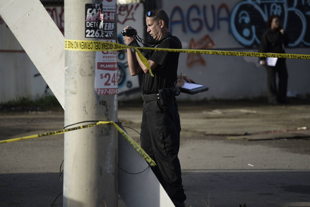 A forensic worker photographs a crime scene where a man was found fatally shot, in San Juan, Puerto Rico, Thursday, Jan. 11, 2018. Thirty-two people have been slain in Puerto Rico in the first 11  ...