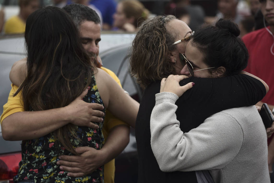 Relatives comfort each other as the body of a family member is removed at an early morning crime scene, in San Juan, Puerto Rico, Thursday, Jan. 11, 2018.  (AP Photo/Carlos Giusti)