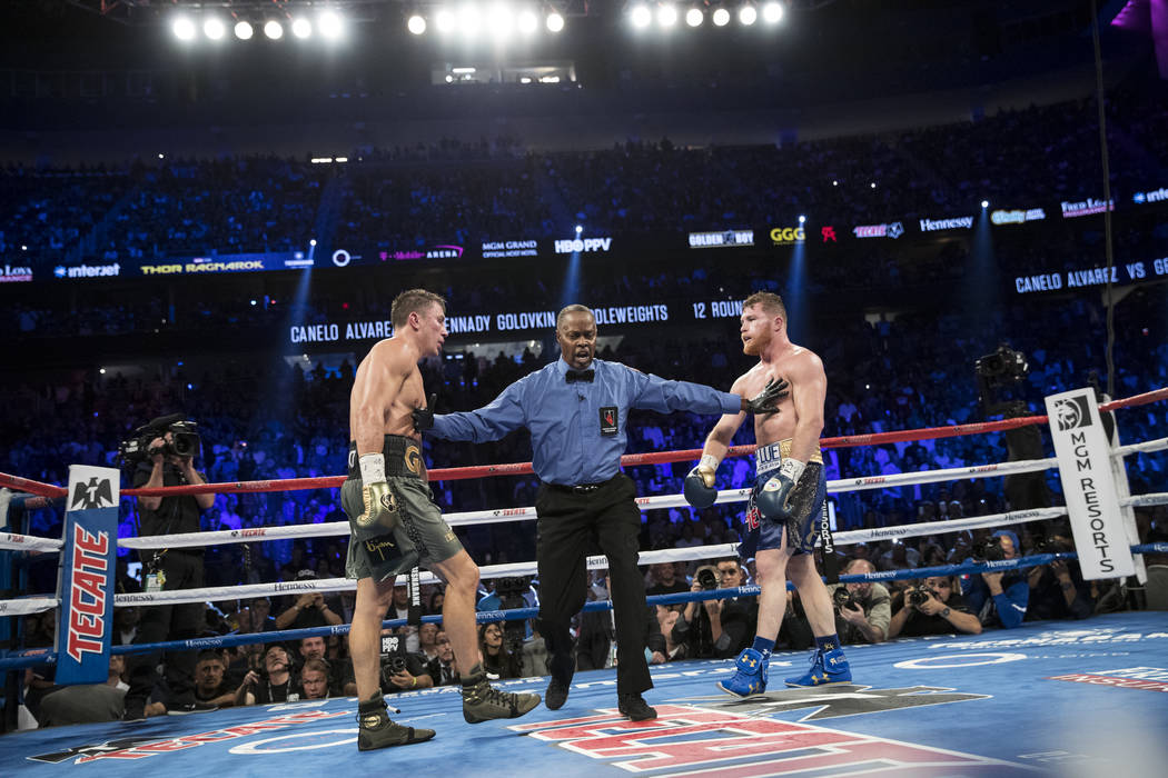 Gennady  Golovkin, left, battles Saul Alvarez in the WBC, WBA, IBF, RING middleweight title bout at T-Mobile Arena in Las Vegas, Saturday, Sept. 16, 2017. The fight ended in a split draw. Erik Ver ...