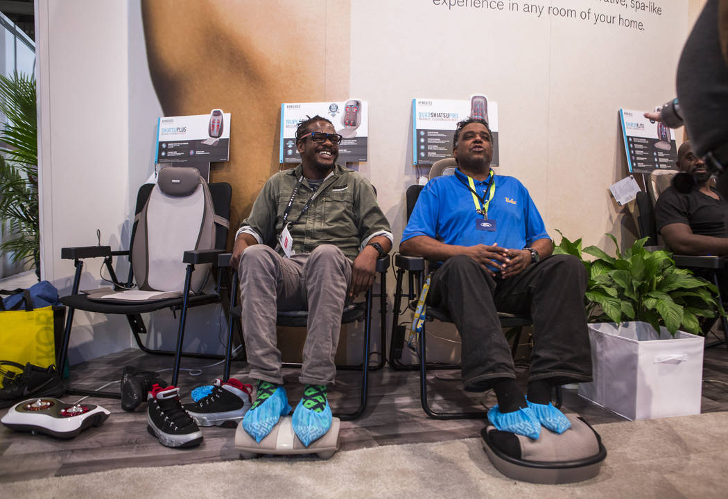 Christopher Cole of Jamaica, left, and Harrison Scott of Los Angeles test Homedics massage chairs at CES in the Las Vegas Convention Center on Thursday, Jan. 11, 2018. Patrick Connolly Las Vegas R ...