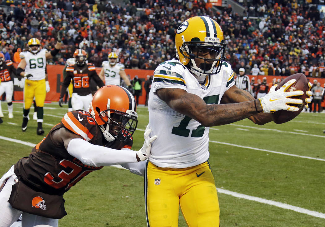 Green Bay Packers wide receiver Davante Adams (17) catches a 1-yard pass for a touchdown under pressure from Cleveland Browns defensive back Jason McCourty (30) in the second half of an NFL footba ...