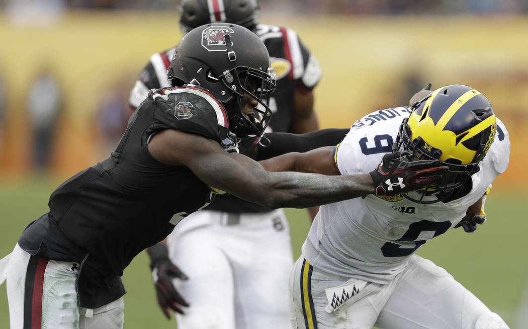 South Carolina defensive back Chris Lammons, left, grabs Michigan wide receiver Donovan Peoples-Jones by the facemask after a reception during the second half of the Outback Bowl NCAA college foot ...