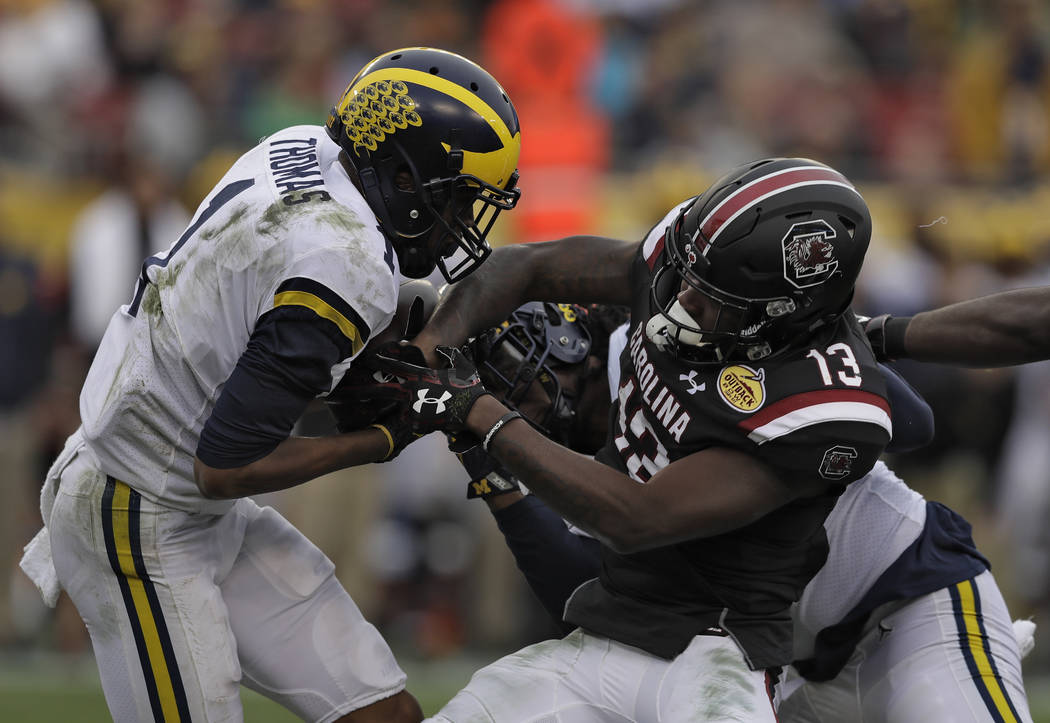 Michigan defensive back Ambry Thomas (1) tries to rip the ball away from South Carolina wide receiver Shi Smith (13) during the first half of the Outback Bowl NCAA college football game Monday, Ja ...