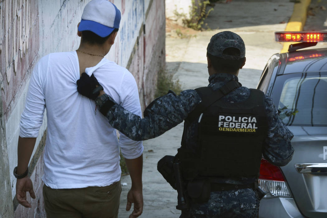 A federal police officer detains a man after a shootout broke out between police and gunmen on a central avenue in downtown Acapulco, Guerrero state, Mexico, Sunday, Nov. 12, 2017. (AP Photo/Berna ...