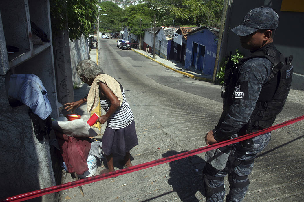 A homeless woman that was sleeping on the street leaves a police secured the area where a man and a woman were found murdred inside a bar in downtown Acapulco, Guerrero state, Mexico, Sunday Nov.  ...