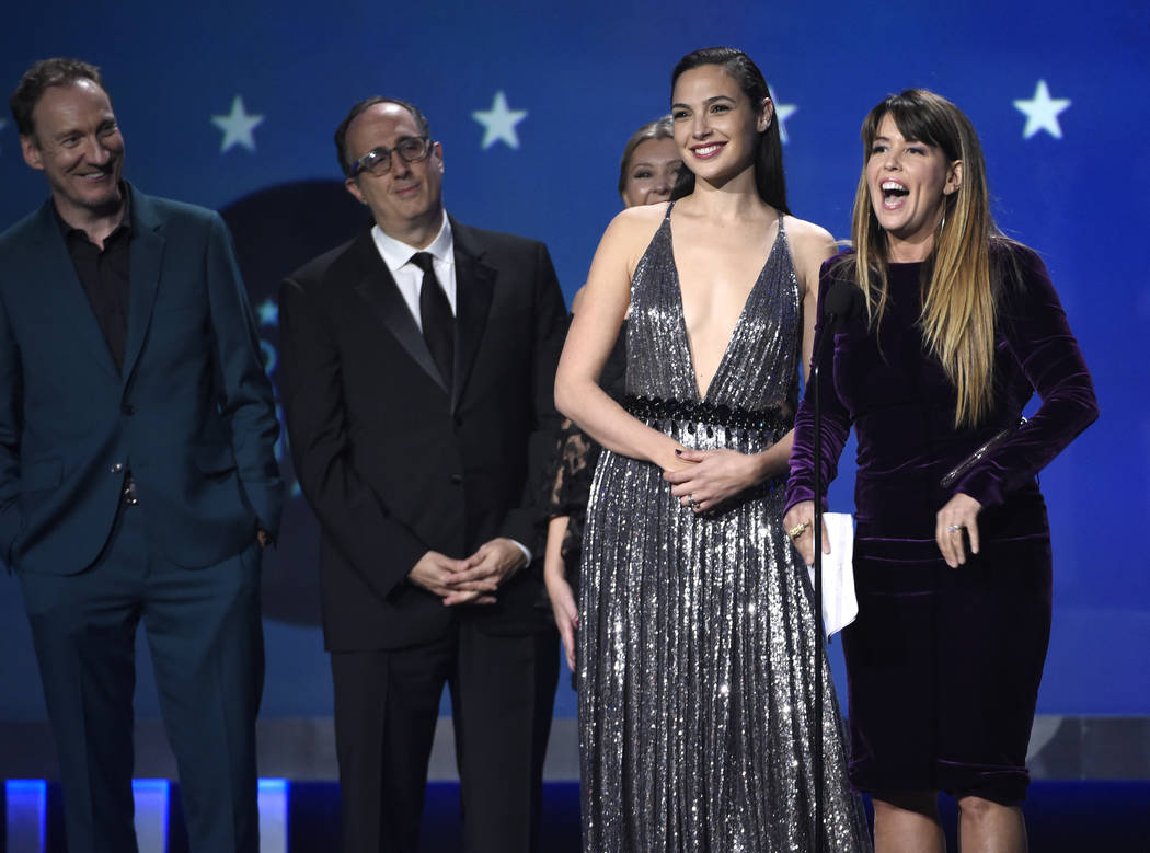 "Gal Gadot, center, Patty Jenkins and the crew of ""Wonder Woman"" accept the award for best action movie at the 23rd annual Critics' Choice Awards at the Barker Hangar on Thursday, ..."