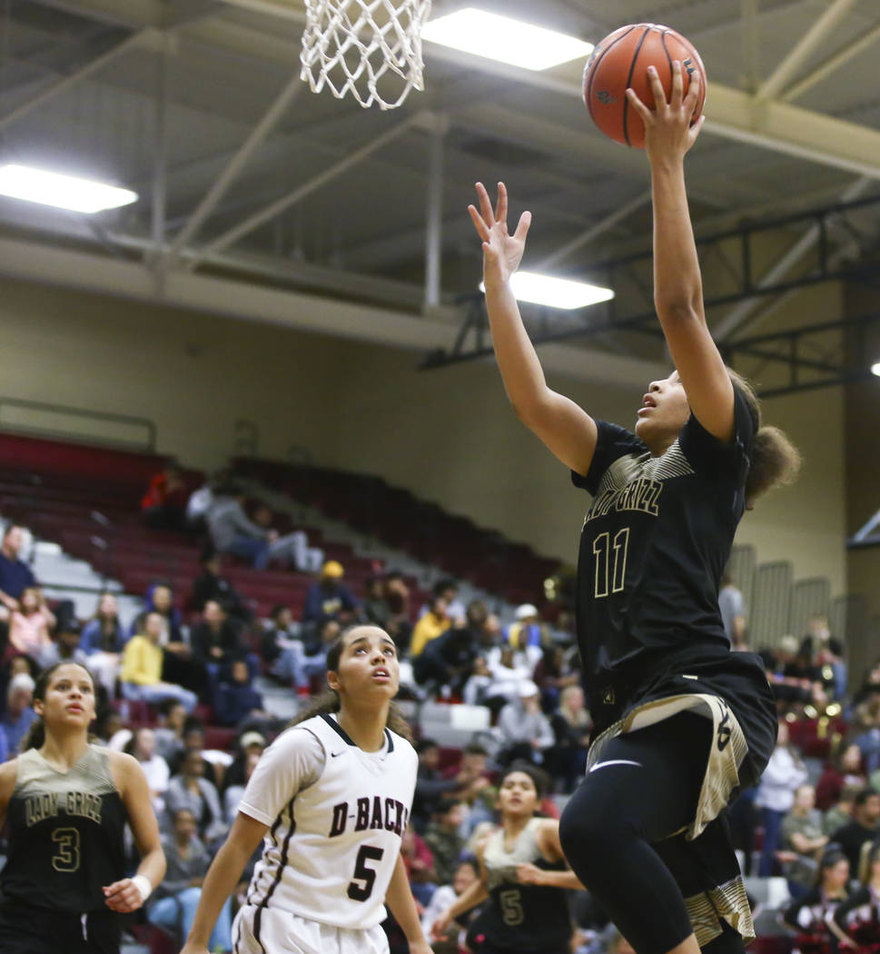 Spring Valley's Kayla Harris (11) goes to the basket over Desert Oasis' Eliyjah Pricebrooks (5) during a basketball game at Desert Oasis High School in Las Vegas on Tuesday, Jan. 16, 2018. Chase S ...