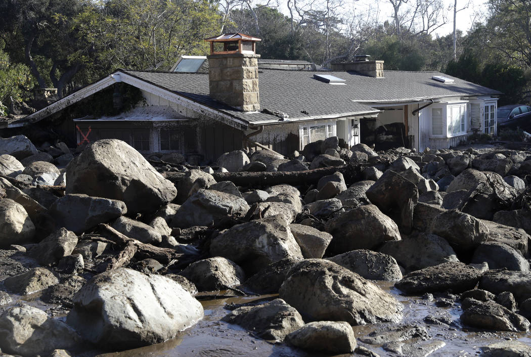 Large rocks and mud are shown in front of a house in Montecito, Calif., Thursday, Jan. 11, 2018. Hundreds of rescue workers slogged through knee-deep ooze and used long poles to probe for bodies T ...