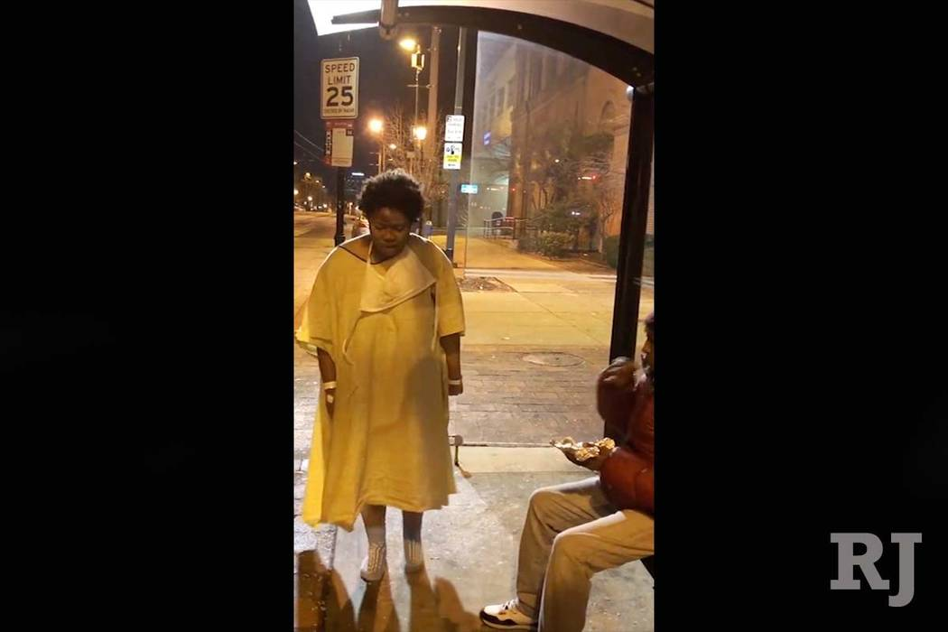A still image taken from video shows a woman discharged from a Baltimore hospital wearing only a gown and socks on a cold winter's night. (Imamu Baraka via AP)