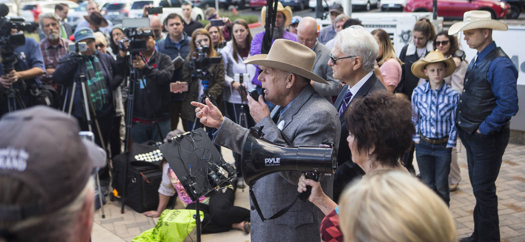 Rancher Cliven Bundy, center, address supporters and journalists at Metropolitan Police Department headquarters two days after federal charges were dismissed against him in Las Vegas on Wednesday, ...