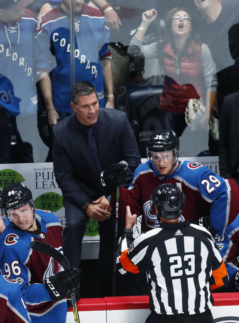 FILE -  In this Thursday, Oct. 19, 2017, file photo, fans react behind the team box as referee Brad Watson, front, talks to Colorado Avalanche head coach Jared Bednar, center left, as center Natha ...