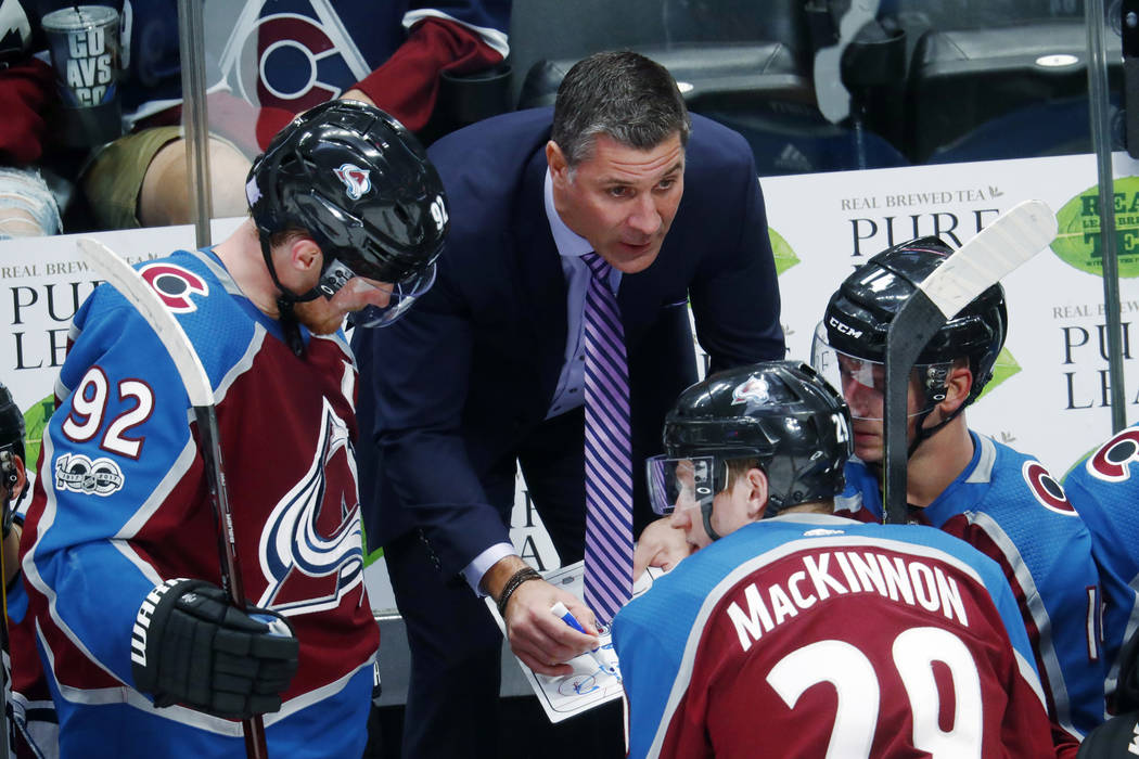 Colorado Avalanche coach Jared Bednar, center, draws up a play for left wing Gabriel Landeskog, left, of Sweden, and center Nathan MacKinnon during a timeout in the third period of an NHL hockey g ...