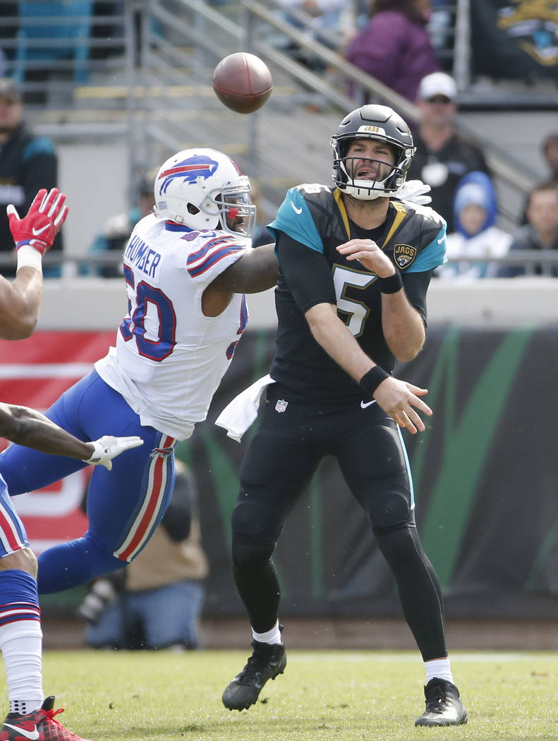 Jacksonville Jaguars quarterback Blake Bortles (5) throws a pass in front of Buffalo Bills outside linebacker Ramon Humber, left, in the first half of an NFL wild-card playoff football game, Sunda ...