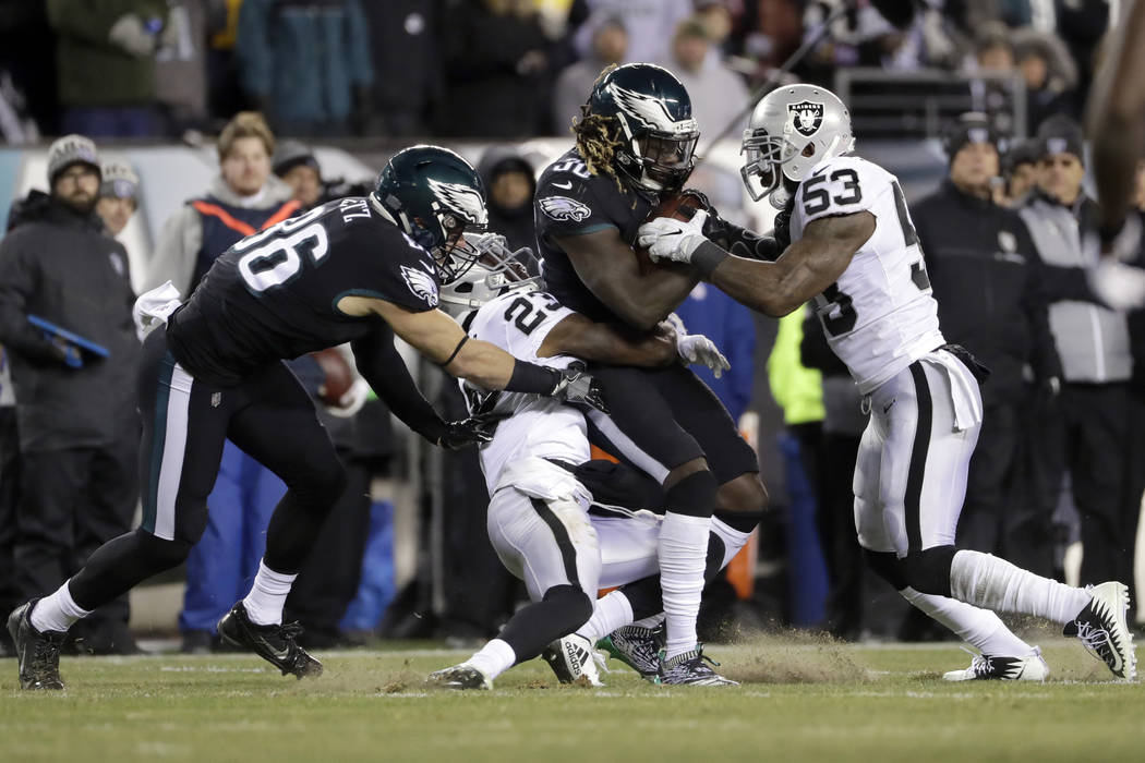 Philadelphia Eagles' Jay Ajayi (36) is tackled by Oakland Raiders' NaVorro Bowman (53) and Dexter McDonald (23) as Zach Ertz (86) defends during the first half of an NFL football game, Monday, Dec ...