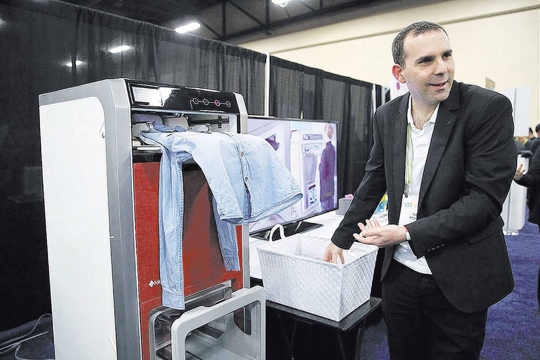 Cal Rozov demonstrates on the FoldiMate, a laundry folding machine, during CES Unveiled at CES International Sunday, Jan. 7, 2018, in Las Vegas. (AP Photo/Jae C. Hong)