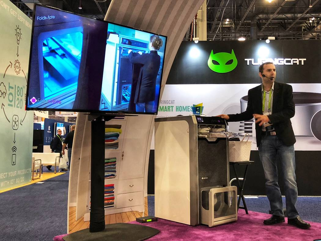 Cal Rozov, a FoldiMate executive, demonstrating the folding appliance at CES on Friday, Jan. 12. (Todd Prince/Review-Journal)