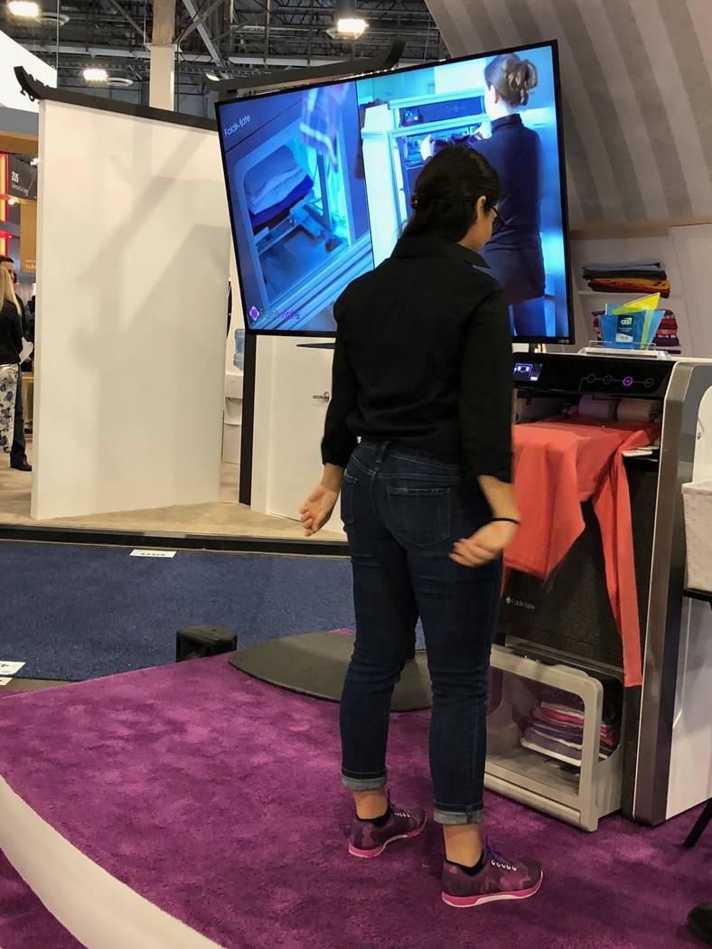 A CES attendee tries the FoldiMate. (Todd Prince/Review-Journal)