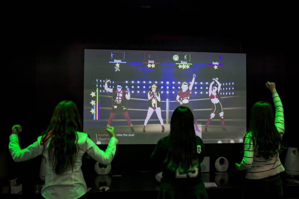 CES attendees play an XBox game on a 150 inch Changhong Smart Cinema at CES at the Las Vegas Convention Center on Friday, Jan. 12, 2018. An estimated 180,000 people attended CES this year. Patrick ...